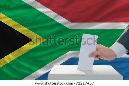 man putting ballot in a box during elections in south africa in front of flag - stock photo