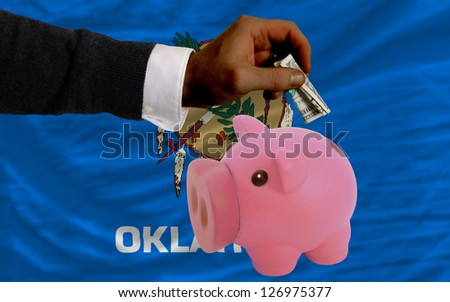 Man putting dollar into piggy rich bank flag of us state of oklahoma in foreign currency because of inflation - stock photo