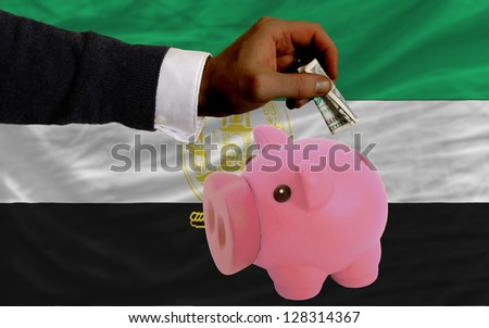 Man putting dollar into piggy rich bank national flag of afghanistan in foreign currency because of inflation - stock photo