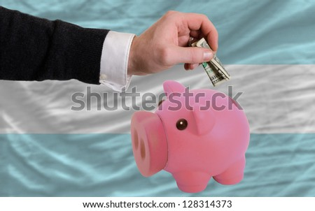 Man putting dollar into piggy rich bank national flag of argentina in foreign currency because of inflation - stock photo