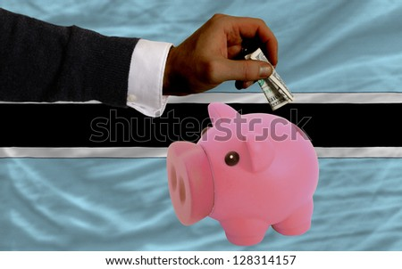 Man putting dollar into piggy rich bank national flag of botswana in foreign currency because of inflation - stock photo