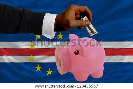 Man putting dollar into piggy rich bank national flag of  cape verde in foreign currency because of inflation - stock photo
