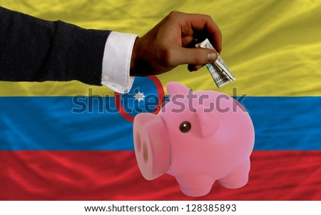 Man putting dollar into piggy rich bank national flag of colombia in foreign currency because of inflation - stock photo