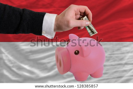 Man putting dollar into piggy rich bank national flag of indonesia in foreign currency because of inflation - stock photo