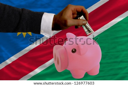 Man putting dollar into piggy rich bank national flag of namibia in foreign currency because of inflation - stock photo