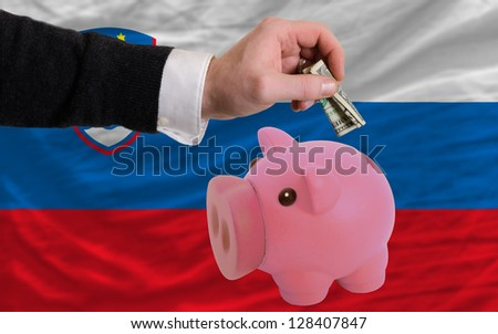 Man putting dollar into piggy rich bank national flag of slovenia in foreign currency because of inflation - stock photo