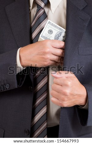 man putting dollars pack into pocket - stock photo