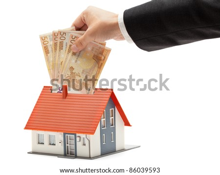 Man putting Euro banknotes into model house - real estate investment concept - stock photo