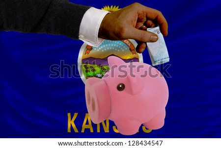 Man putting euro into piggy rich bank and flag of us state of kansas in foreign currency because of insecurity and inflation - stock photo