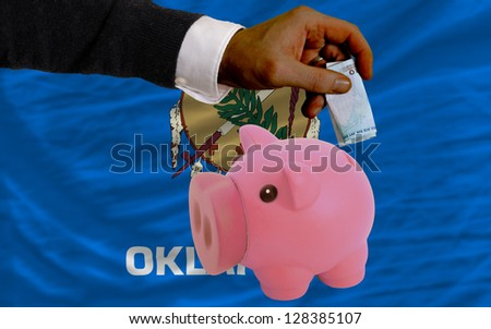 Man putting euro into piggy rich bank and flag of us state of oklahoma in foreign currency because of insecurity and inflation - stock photo