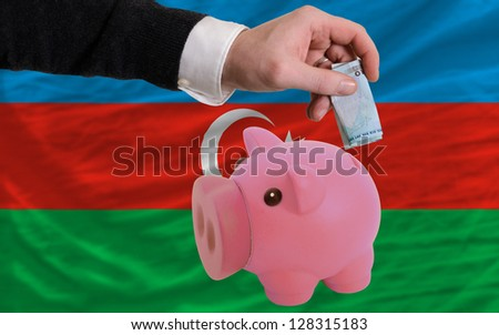 Man putting euro into piggy rich bank and national flag of azerbaijan in foreign currency because of insecurity and inflation - stock photo