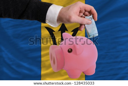 Man putting euro into piggy rich bank and national flag of barbados in foreign currency because of insecurity and inflation - stock photo