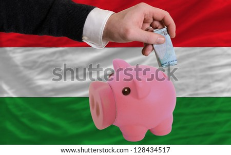 Man putting euro into piggy rich bank and national flag of hungary in foreign currency because of insecurity and inflation - stock photo