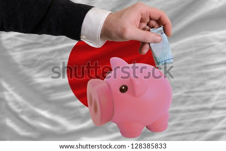 Man putting euro into piggy rich bank and national flag of japan in foreign currency because of insecurity and inflation - stock photo