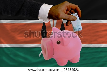 Man putting euro into piggy rich bank and national flag of kenya in foreign currency because of insecurity and inflation - stock photo