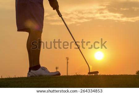 Man putting golf ball against sunset - stock photo