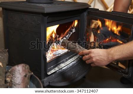 Man Putting Log Onto Wood Burning Stove - stock photo