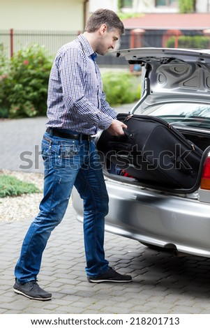 Man putting luggage into car trunk, vertical - stock photo