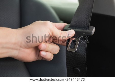 Man putting on his seat belt in his car - stock photo