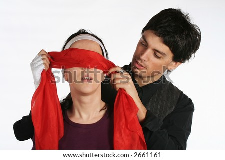 Man putting red blindfold on woman eyes. Happy love couple game - stock photo
