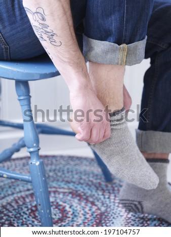 Man putting socks on, close-up - stock photo