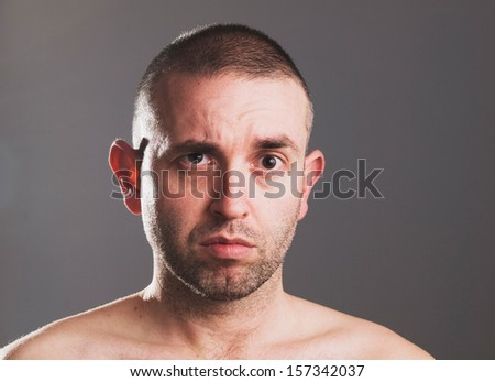 Man raising his eyebrow with surprise expression and isolated on grey background. - stock photo