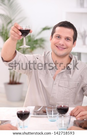 Man raising his glass for a toast - stock photo