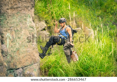man rapelling down mountainside in free air wearing blue and black clothing - stock photo