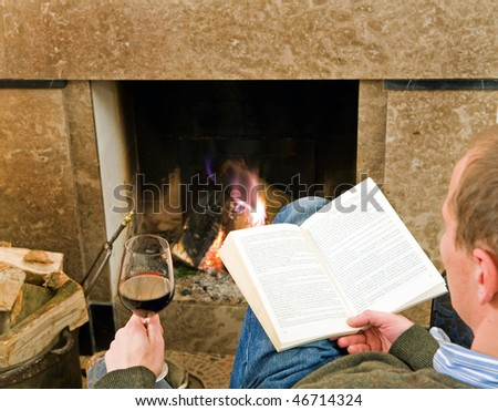 Man reading a book and drinking a glass of wine by the fireplace, relaxing. - stock photo