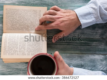 Man reading a book and writing notes on wooden table - stock photo