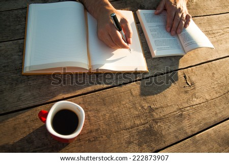 Man reading a book and writing notes on wooden table on sunset. - stock photo