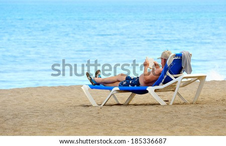 Man reading a book on a beach - stock photo