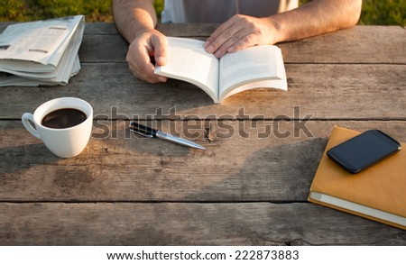 Man reading a book on wooden table with coffee, notes and smart phone. - stock photo
