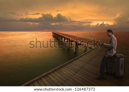 man reading a guide book on wood bridge before travel to another place - stock photo
