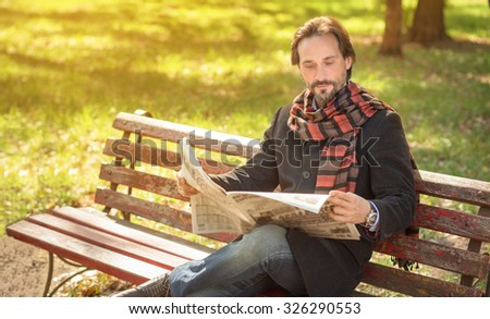 Man reading about the current events in the newpaper in the park. Handsome man resting on the bench in autumn season. - stock photo