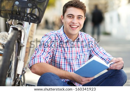 Man reading book outdoors - stock photo