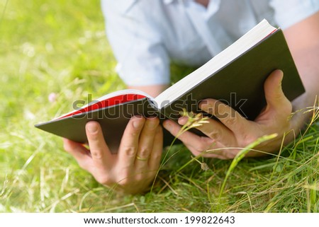 Man reading book outside - stock photo