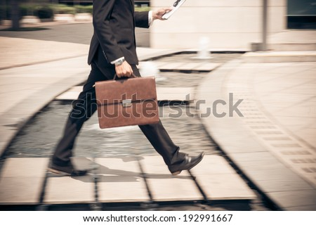 Man reading newspaper while hurrying to work - stock photo