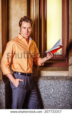 Man Reading Outside. Dressing in a light orange patterned shirt, gray pants, a young handsome guy is standing by an old fashion window in the corner, reading a red book, thinking.  - stock photo