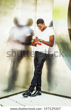 Man Reading Outside. Wearing a white V neck T shirt, pants, leather shoes, wristwatch, a young black guy is leaning back against  metal mirror walls, looking down, turning pages, reading a red book.  - stock photo