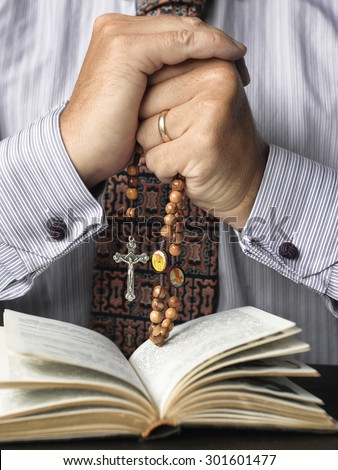 Man reading the bible and praying the rosary - stock photo
