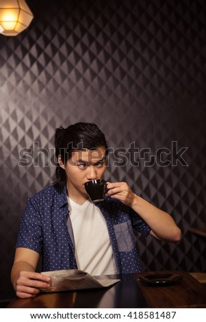 Man reading the newspaper and drinking coffee in a coffee shop - stock photo