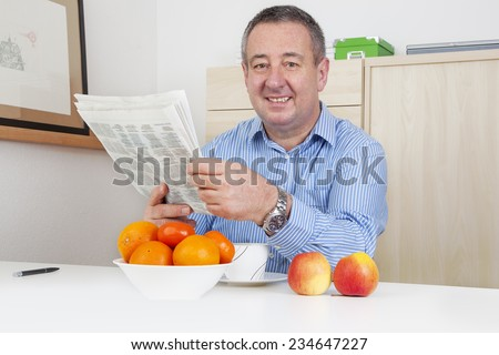 Man reading the newspaper in his spare time - stock photo