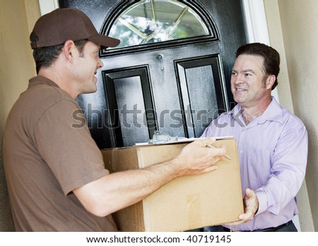 Man receiving a package delivery from a courier at his home. - stock photo