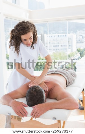 Man receiving back massage in spa centre - stock photo