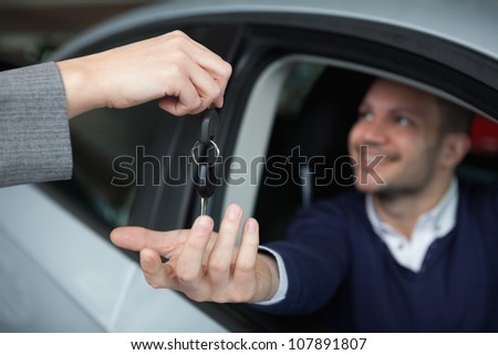 Man receiving car keys while sitting in his car in a garage - stock photo