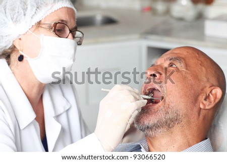 Man receiving dental inspection from dentist - stock photo