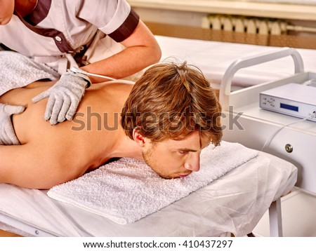 Man receiving electricity gloves massage at beauty salon. - stock photo