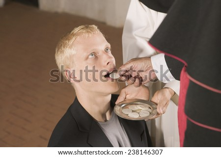 Man Receiving Host from Priest - stock photo