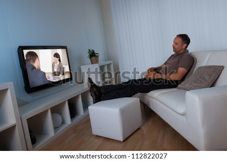 Man recline comfortably on his living room couch watching home movies on his widescreen television set - stock photo